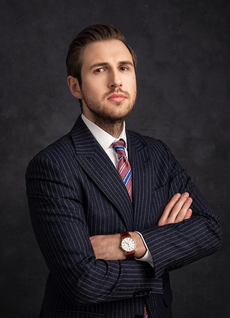 Sesja profesjonalna, portret przedsiębiorcy na ciemnym tle w studio